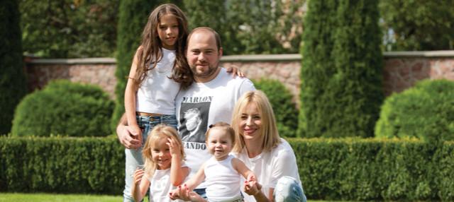 Вадим Столар з дружиною Інною Майструк та дітьми на фоні муру довкола родинного маєтку